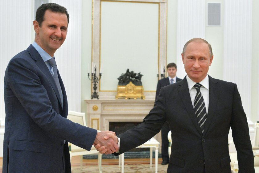 FILE - In this Tuesday, Oct. 20, 2015 file photo, Russian President Vladimir Putin, right, shakes hand with Syria President Bashar Assad in the Kremlin in Moscow, Russia. Russia's involvement in Syria has led to resumed talks about Syria's future in Vienna. So far there's no progress but at least t