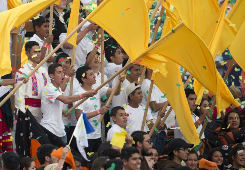 Confetti rains down on flag-bearers at the end of a meeting between Mexican youth and Pope Francis, at Jose Maria Morelos y Pavon Stadium in Morelia, Mexico, Tuesday, Feb. 16, 2016. On his one-day trip to the capital of the Michoacan state, Francis also celebrated mass and visited the Morelia cathe