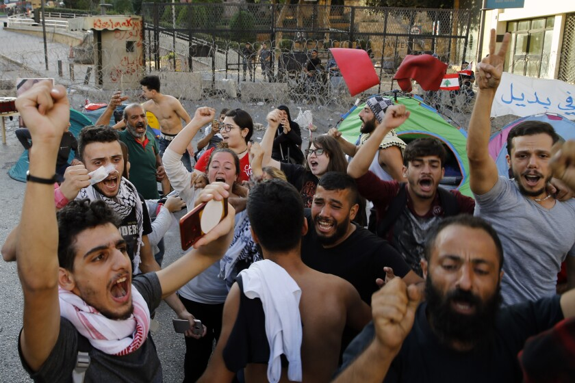 Anti-government protesters celebrate after Lebanon Prime Minister Saad Hariri announced his resignation on Tuesday in Beirut.