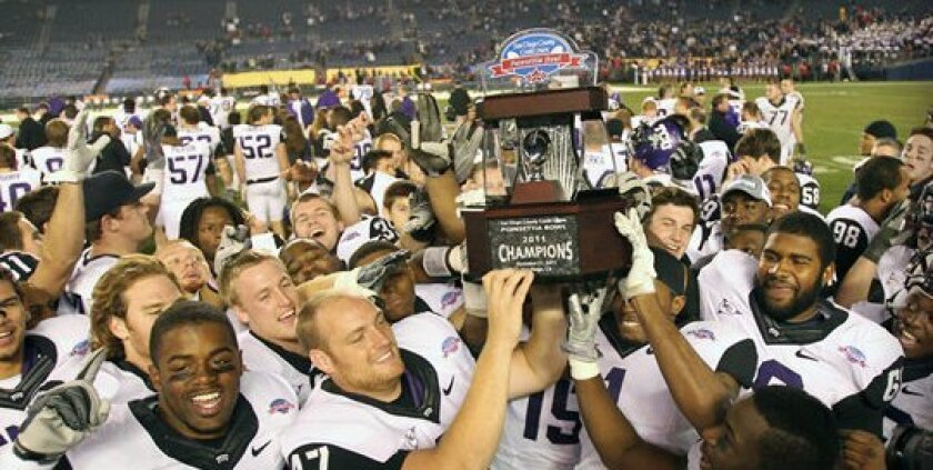 TCU holds up the Poinsettia Bowl trophy after beating Louisiana Tech on Wednesday night. Courtesy TCU athletics.