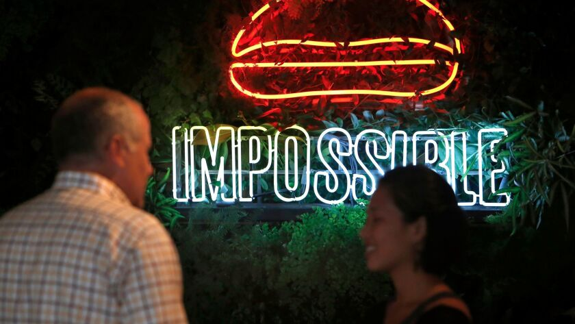 People talk in front of an impossible burger sign at an Umami Burger in downtown Los Angeles,