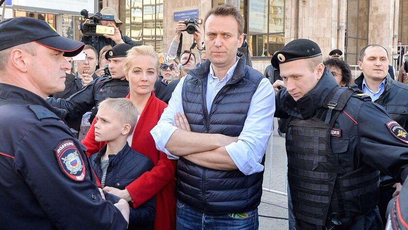 Russian opposition leader Alexei Navalny, center, his wife, Yulia, and their son, Zahar, talk to pol