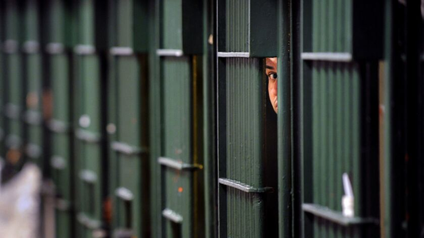 An inmate peeks through bars at the Men's Central Jail in Los Angeles.
