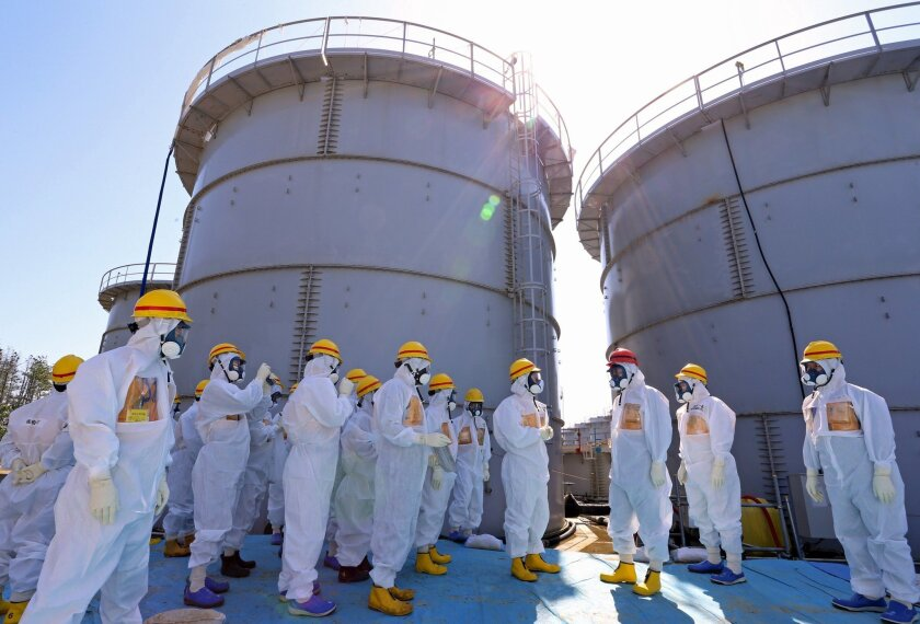 FILE - In this Thursday, Sept. 19, 2013 file photo, Japanese Prime Minister Shinzo Abe, third right, wearing a red helmet, is briefed about tanks containing radioactive water by Fukushima Dai-ichi nuclear power plant chief Akira Ono, fourth right, during his inspection tour to the tsunami-crippled plant in Okuma, Fukushima Prefecture, northeastern Japan, following a series of radioactive water leak from the tanks. A government panel proposed additional measures to lessen the contaminated water crisis at Japan's crippled nuclear power plant, saying Tuesday, Dec. 3, that current plans are not enough to prevent the risk of a disaster. (AP Photo/Japan Pool, File) JAPAN OUT
