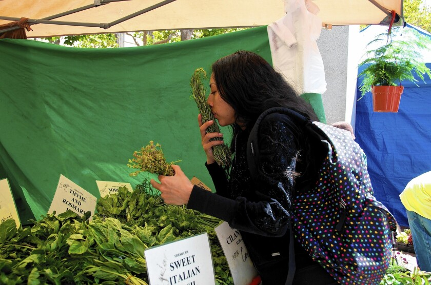 Mercy Mena, 25, uses her Supplemental Nutrition Assistance Program benefits at Heart of the City Farmers Market in San Francisco. Other California farmers markets have also begun to reach more consumers who receive nutritional benefits.