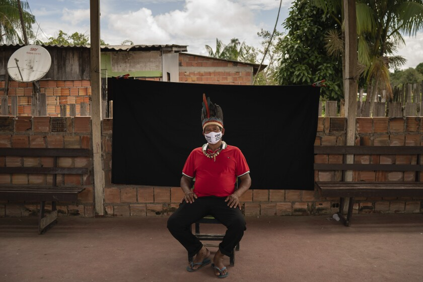 "Indigenous leader Jose Augusto, 48, of the Miranha indigenous ethnic group, poses for a portrait wearing a face mask amid the spread of the new coronavirus, at the Park of Indigenous Nations community in Manaus, Brazil, Thursday, May 28, 2020. His mask reads in Portuguese: ""Indigenous lives matter."" (AP Photo/Felipe Dana)"