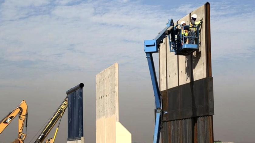 Dos trabajadores laboran en uno de los prototipos del muro fronterizo entre México y Estados Unidos.