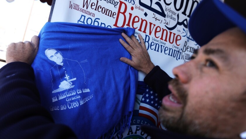 """Oscar Levi Dominguez, 45, president and founder of El Salvador Corridor, holds a scarf with an image of Oscar Romero. The scarf carries a quote from Romero, """"Martyrdom is a grace that I do not believe I deserve."""""""