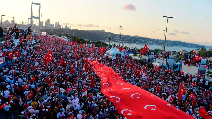 People stand under a collection of Turkish national flags as they gather on the recently renamed July 15 Martyrs Bridge over the Bosporus in Istanbul.