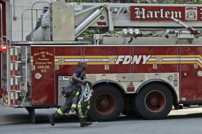 """In this Saturday, Aug. 15, 2015 photo, a firefighter with Fire Department of New York Engine 69/Ladder 28, the """"Harlem Hilton"""", rushes to the firetruck after receiving a call during an FDNY block party in the Harlem neighborhood of New York. At 150 years old, the nation's largest fire department is undergoing a massive shift in hiring and recruitment after a court ordered changes to diversity the almost all-white, all-male department. (AP Photo/Mary Altaffer)"""