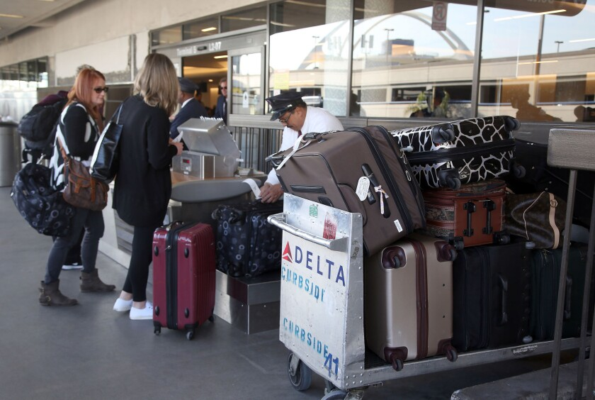 Passengers check their luggage at LAX.