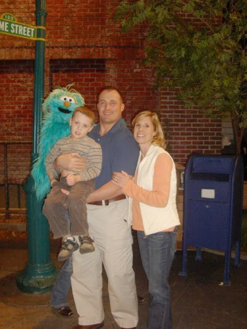 "Nick Marcolongo, his wife, LIsa, and son Rocco are seen on the Sesame Street set, which Nico said ""was almost surreal. There I was sitting on the steps at 123 Sesame Street, walking around Mr. Hooper's store and climbing in Oscar's trash can."""