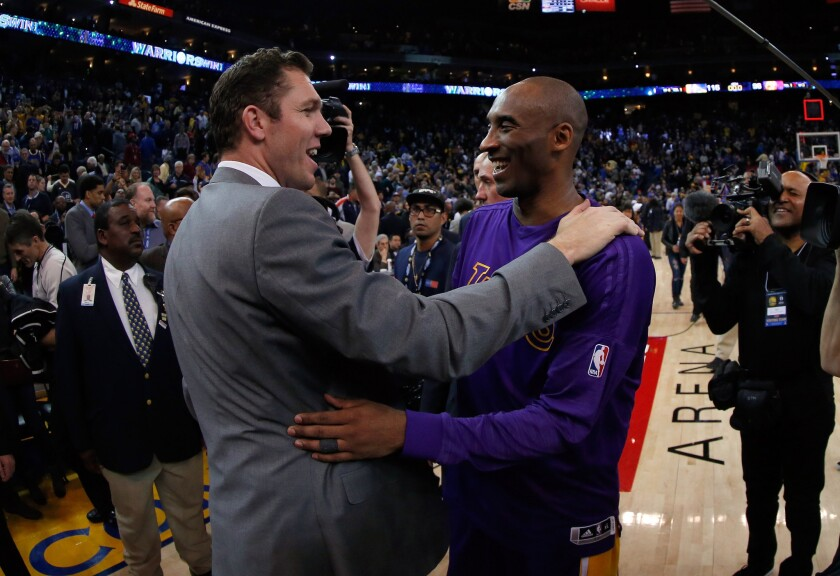 Kobe Bryant hugs Luke Walton, who was serving as the Golden State Warriors interim head coach, after a game.