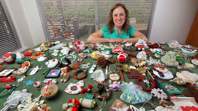 Sheryl Neal with a table full of holiday ornaments she received while participating in a ornament exchange with friends years ago.