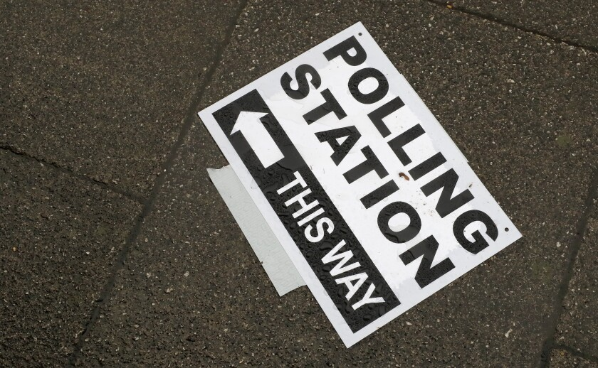 FILE - In this Thursday, Dec. 12, 2019 file photo, a polling station signpost lies on the pavement, in Twickenham, England. The British government announced Tuesday May 11, 2021, contentious plans to toughen election voting rules by requiring photo identification at polling stations, a move it says will protect the democratic system against electoral fraud. (AP Photo/Frank Augstein, File)
