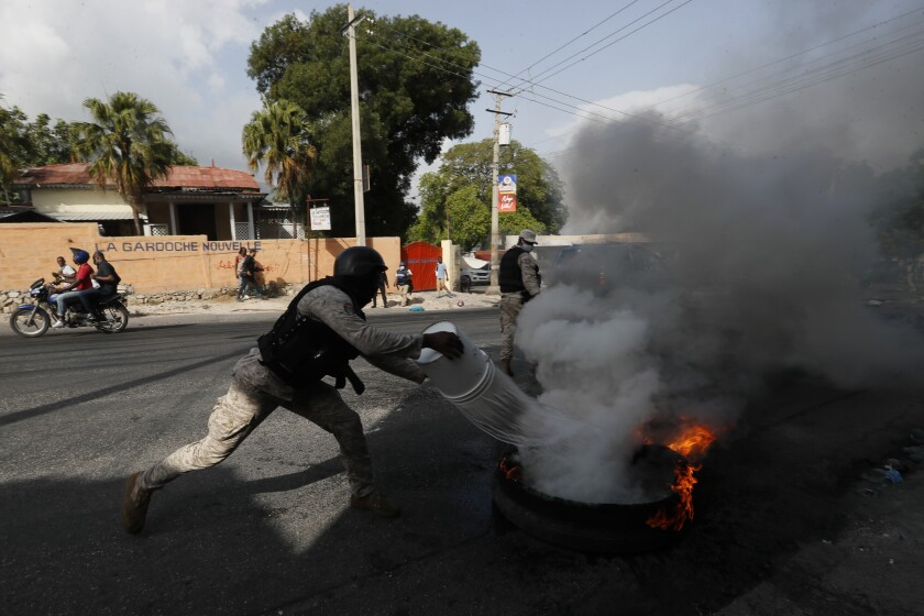 Police put out a burning tire set fire by protesters upset with growing violence in the Lalue neighborhood of Port-au-Prince, Haiti, Wednesday, July 14, 2021. Haitian President Jovenel Moise was assassinated on July 7. (AP Photo/Fernando Llano)
