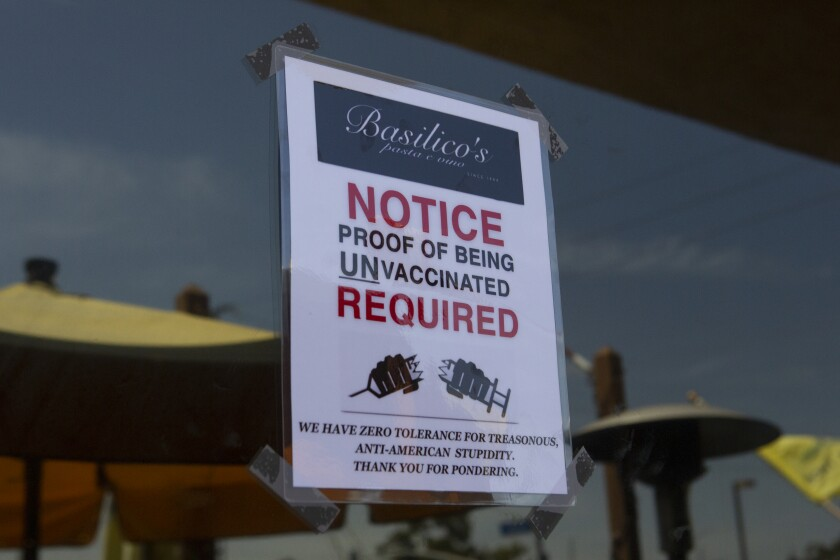 A sign outside Basilico's restaurant in Huntington Beach says patrons must be unvaccinated to enter.