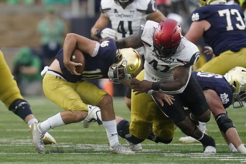 Notre Dame quarterback Drew Pyne (10) is sacked by Cincinnati's Malik Vann (42) during the second half of an NCAA college football game, Saturday, Oct. 2, 2021, in South Bend, Ind. Cincinnati won 24-13. (AP Photo/Darron Cummings)