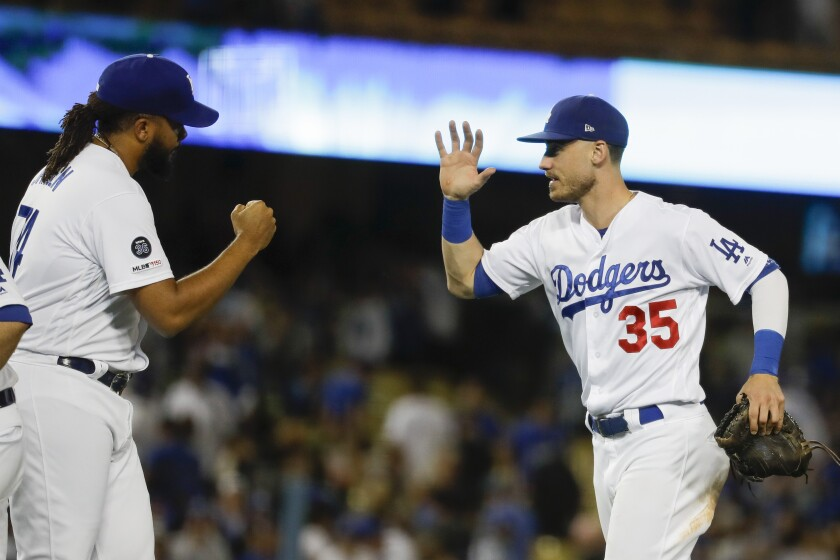 Dodgers right fielder Cody Bellinger, right, celebrates after their 7-5 win against the Tampa Bay Rays with relief pitcher Kenley Jansen on Tuesday at Dodger Stadium.