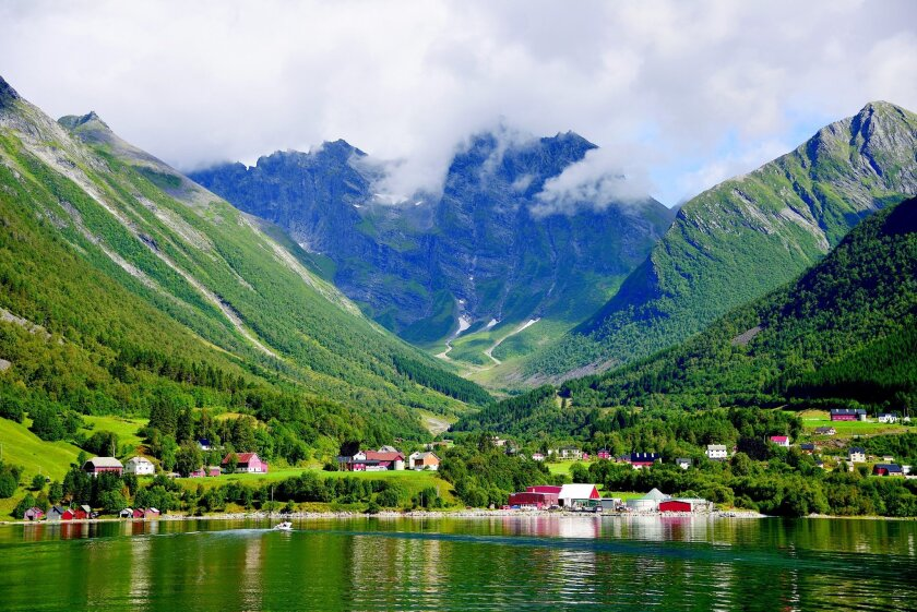 Pastoral villages dot the landscape along the picturesque Geirangerfjord in Norway.