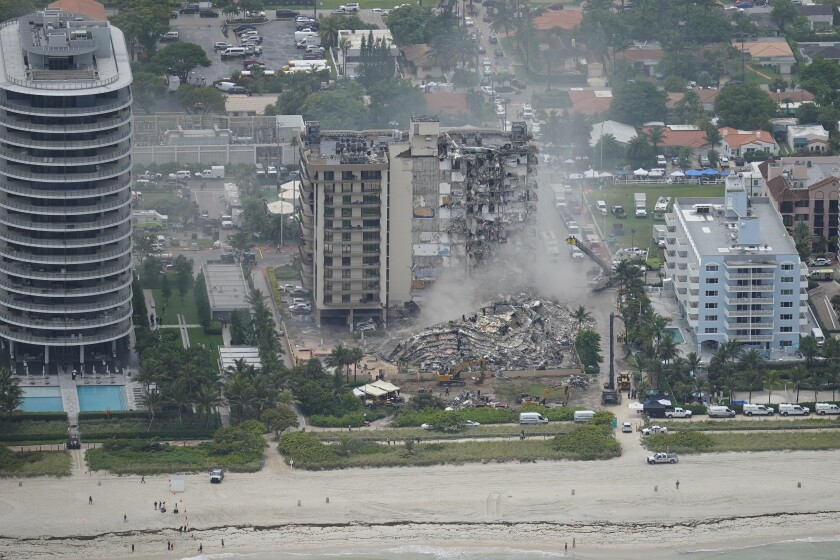 Rubble appears in front of a partly collapsed tower among a row of beachfront buildings.