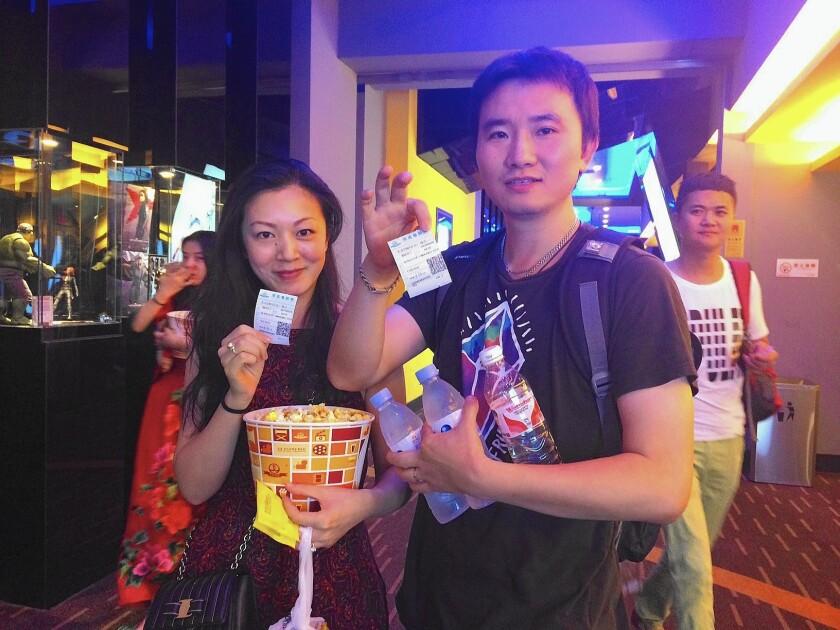 "Zhou Yuan, 31, and Zhang Chao, 36, head into a screening of ""Jurassic World"" in Beijing on June 16, 2015."