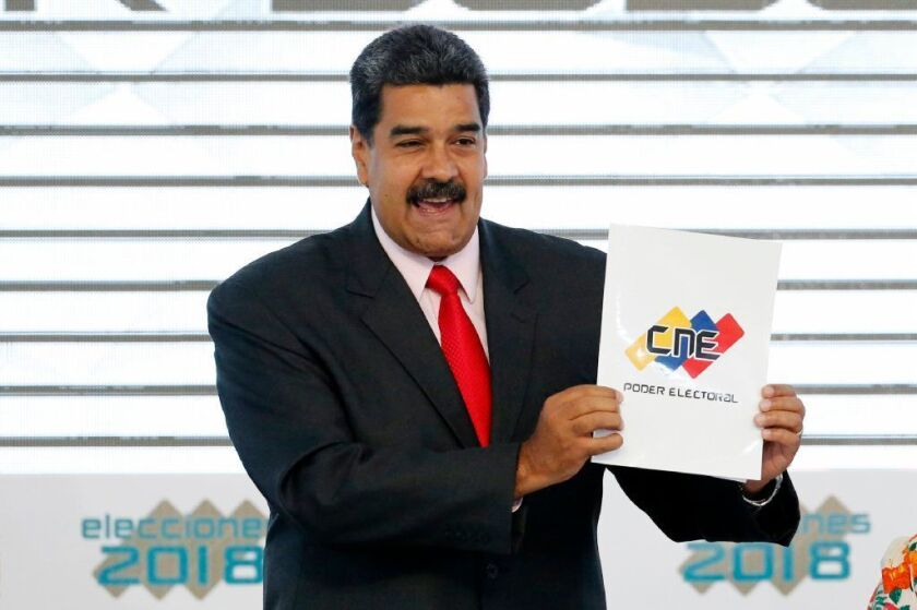 Venezuela's President Nicolas Maduro holds up the National Electoral Council certificate declaring him the winner of the presidential election, during a ceremony at CNE headquarters in Caracas,