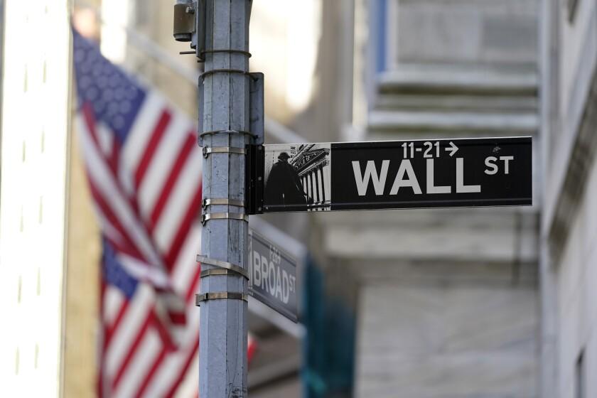 Fotografía de archivo del 16 de junio de 2021 de banderas ondeando en la fachada de la Bolsa de Valores de Nueva York, atrás de un letrero con el nombre de su calle. (AP Foto/Richard Drew)