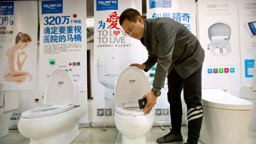 Zhong Jiye, co-founder of Shenzhen Trump Industrial Co., demonstrates one of his firm's high-end Trump-branded toilets at a showroom in Shenzhen in southern China on Feb. 13, 2017.