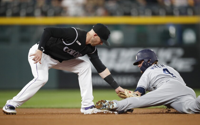 Rockies shortstop Trevor Story, left, tags the Padres' Wil Myers on a steal attempt. Myers beat the throw but was called out for coming off the bag.