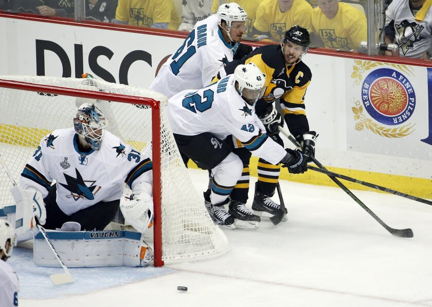 Pittsburgh Penguins' Sidney Crosby, right, centers the puck past San Jose Sharks' Joel Ward (42) as Sharks goalie Martin Jones (31), defends during the first period in Game 1 of the Stanley Cup final series Monday, May 30, 2016, in Pittsburgh. (AP Photo/Gene J. Puskar)