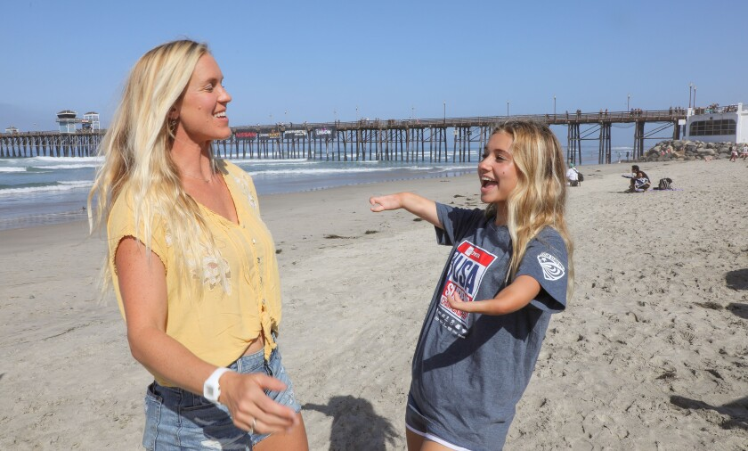 At the Super Girl Surf Pro contest at the Oceanside Pier, pro surfer Bethany Hamilton, of Hawaii, at left, who lost her left arm in a shark attack, chats with surfer Liv Stone, 16, of Carlsbad, at right, who was born with a congenital deformity of her arms