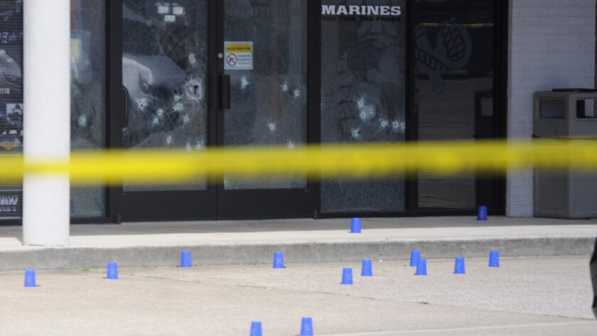 Blue shell-casing markers are scattered outside the military recruiting center, where the attack began.
