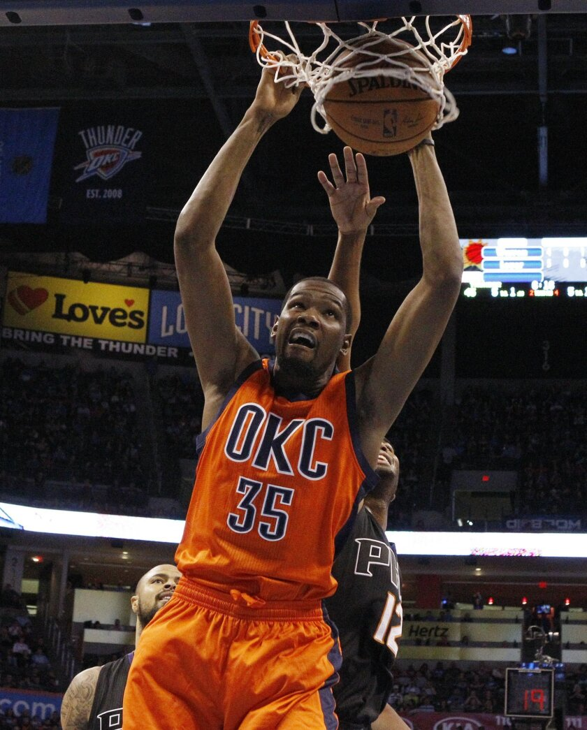 Oklahoma City Thunder forward Kevin Durant (35) dunks in front of Phoenix Suns forward T.J. Warren (12) in the second quarter of an NBA basketball game in Oklahoma City, Sunday, Nov. 8, 2015. (AP Photo/Sue Ogrocki)