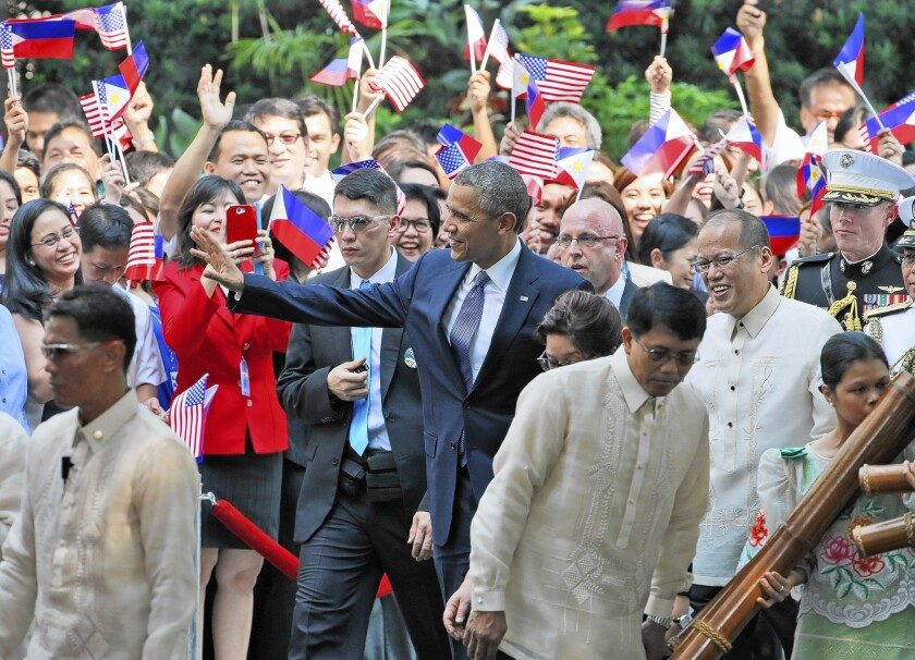 President Obama waves as he walks at Malacanang Palace in Manila. Obama was on the last stop of his four-nation Asian trip.
