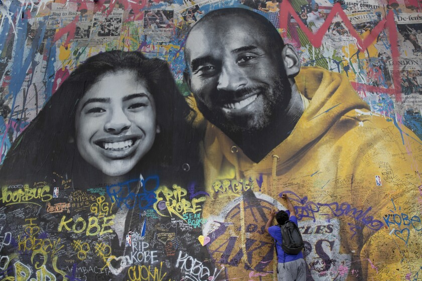 Ernest Wilson of Dallas, Texas writes a message on Thierry Guetta's mural in the 1200 block of S. La Brea Ave. on Feb. 27.