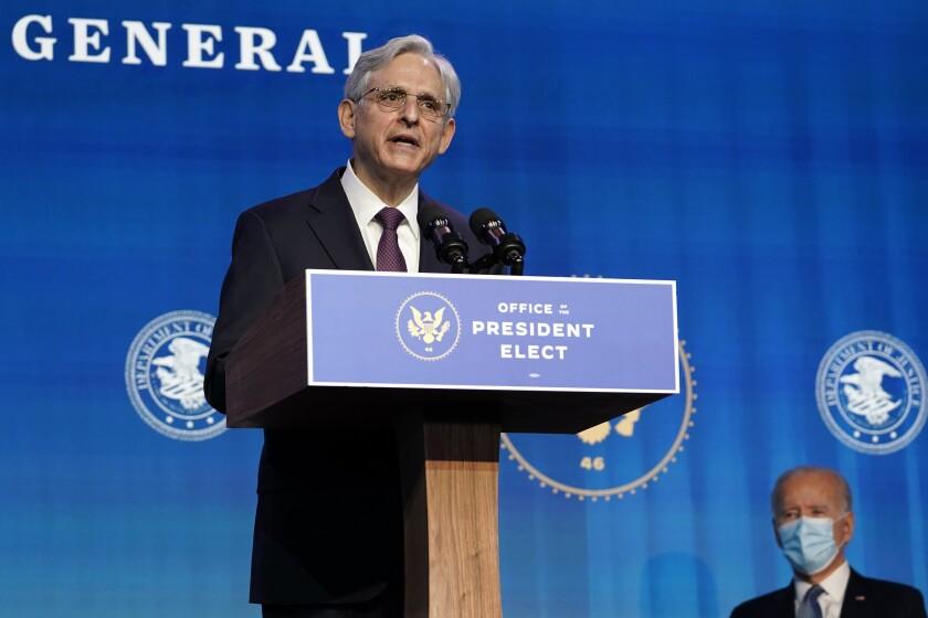 Merrick Garland at a lectern, with Joe Biden at right