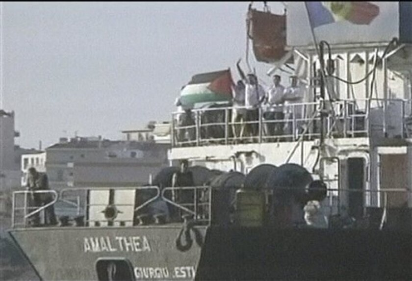 In this image taken from undated video footage, people on board the Amalthea wave Palestinian flag at sea in unknown country. A Libyan boat carrying supplies for Gaza was sailing toward Egypt late Tuesday, July 13, 2010 instead of trying to run a naval blockade of the Palestinian territory, Israeli