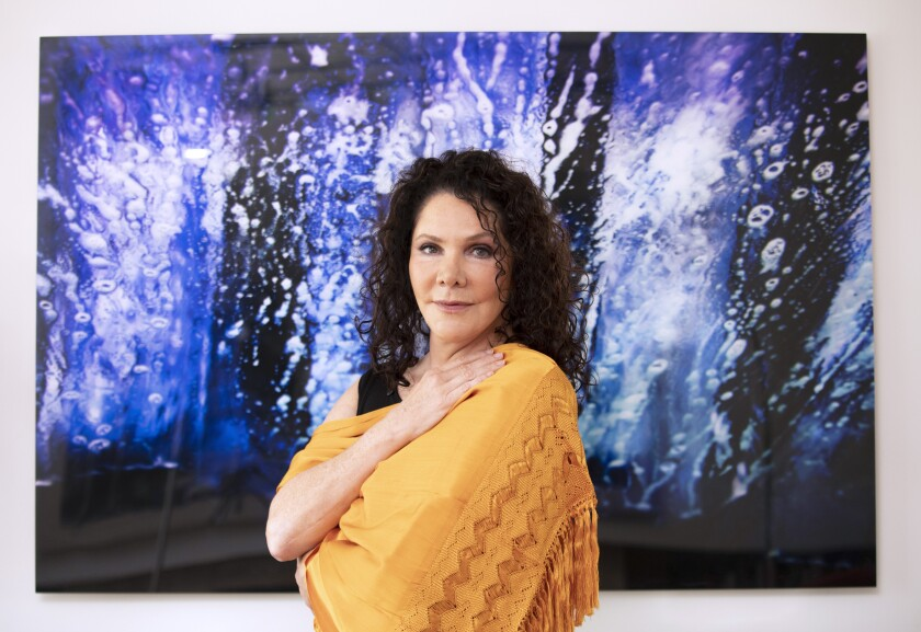 Author María Amparo Escandón wears a gold shawl and stands in front of a blue painting.