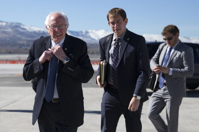 Democratic presidential candidate, Sen. Bernie Sanders, I-Vt. adjusts his tie as he walks to address the media before departing the airport for campaign events in Colorado, Saturday, Feb. 13, 2016, in Reno, Nev. (AP Photo/Evan Vucci)