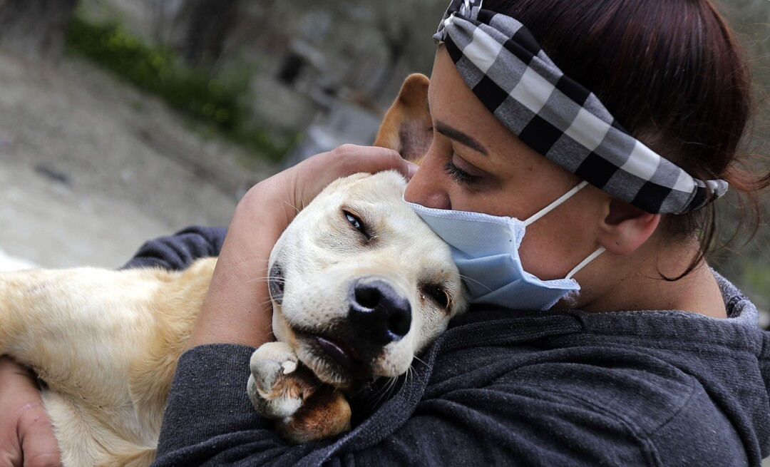 LEBANON: Zaynab Razzouk, head of the animal protection NGO Carma, hugs a dog at the shelter in the area of Koura, north of the Lebanese capital Beirut on April 3, 2020. - According to Razzouk, dogs and cats are getting dumped every day as a result of the outbreak of Covid-19.