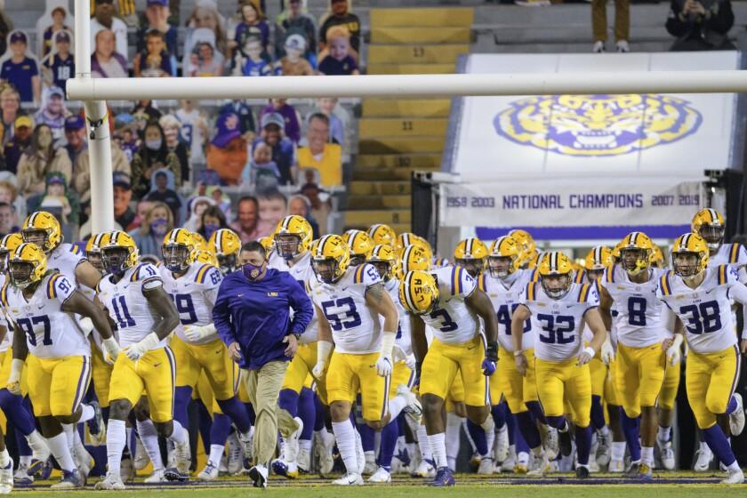 LSU head coach Ed Orgeron leads his team on the field before an NCAA college football game against Alabama in Baton Rouge, La., Saturday, Dec. 5, 2020. (AP Photo/Matthew Hinton)