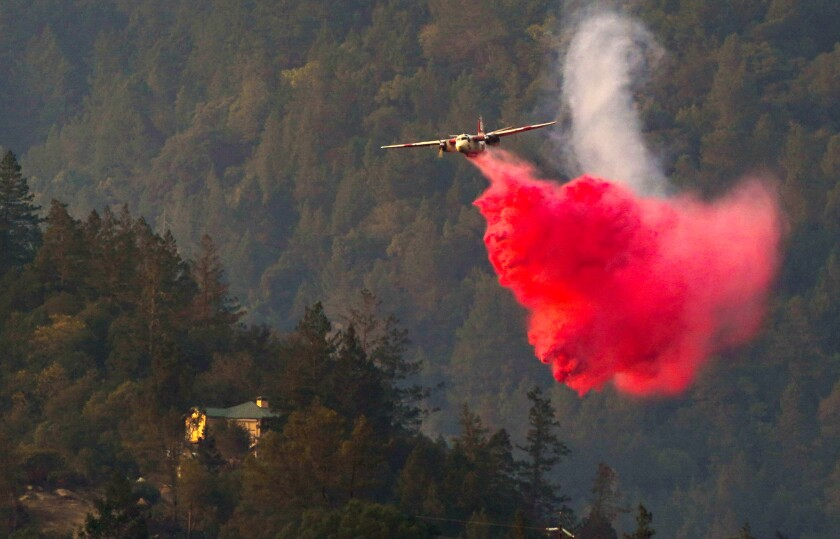 An aircraft drops a red cloud of fire retardant on tree-covered hills near California 29 in Calistoga.