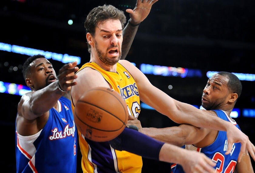 Lakers power forward Pau Gasol loses control of the ball against the double-team defense of Clippers center DeAndre Jordan, left, and forward Willie Green in the first half.