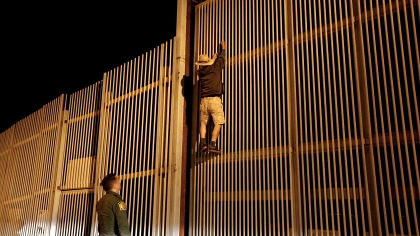 Eduardo Olmos, 38, U.S. Border Patrol agent, apprehends a Mexican man trying to climb the secondary