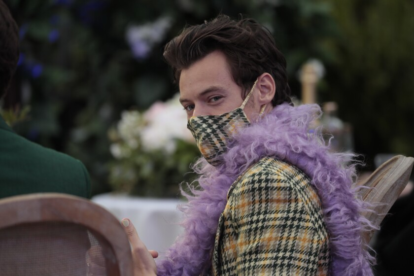 A man with brown hair in a plaid mask, matching blazer and purple boa