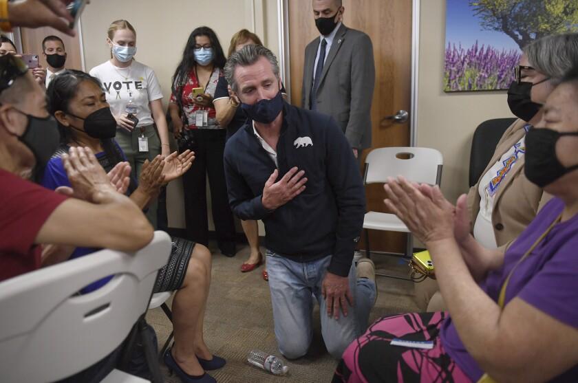 California Gov. Gavin Newsom, center, receives applause from former farmworkers