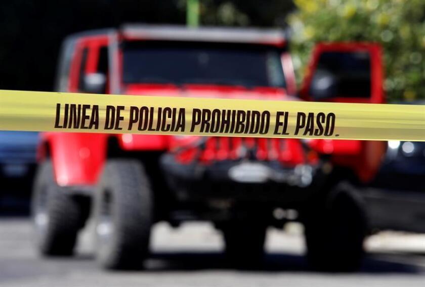 Agentes ministeriales y policías resguardan el lugar donde un funcionario adscrito a la cuarta visitaduría de la Comisión Estatal de Derechos Humanos fue interceptado por un grupo armado cuando viajaba en su vehículo hoy, viernes 24 de noviembre de 2017, en Guadalajara (Mexico). EFE