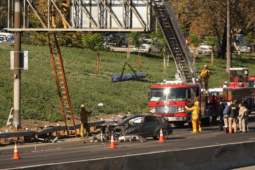 Firefighters use a ladder truck to remove the body of a 20-year-old man whose body landed on a freeway sign after he was ejected from a vehicle during a crash in Glendale on Oct 30.