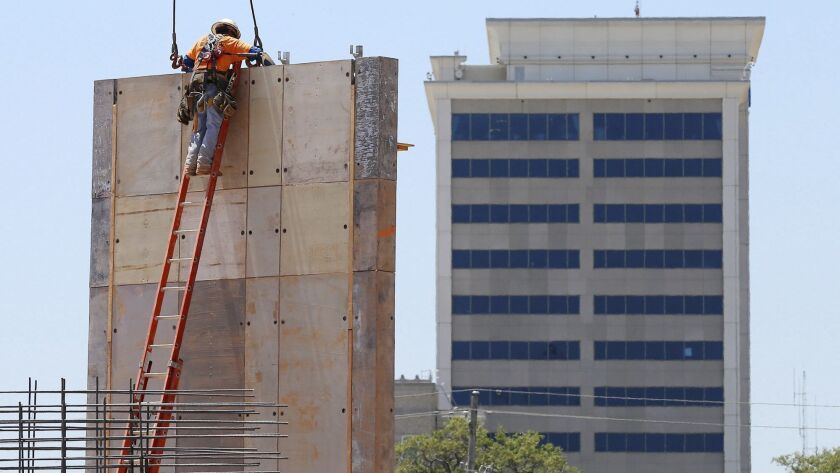 A construction worker removes crane cables from a concrete wall in Gulfport, Miss.